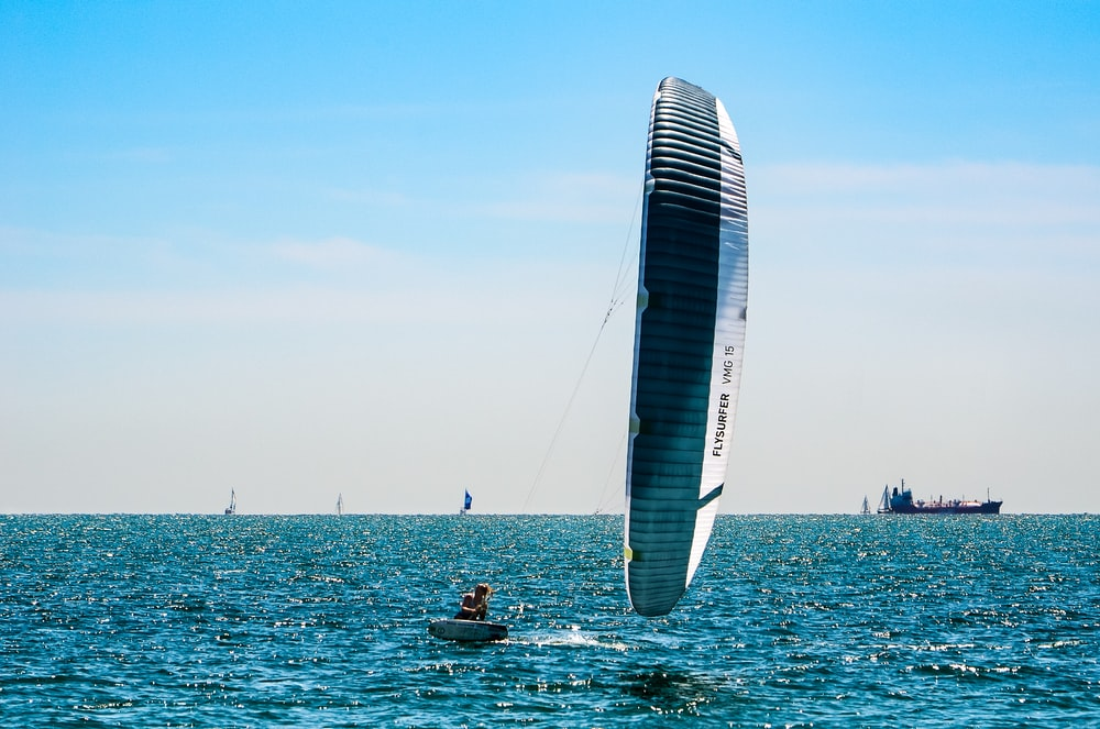 people riding on white and blue sail boat on sea during daytime