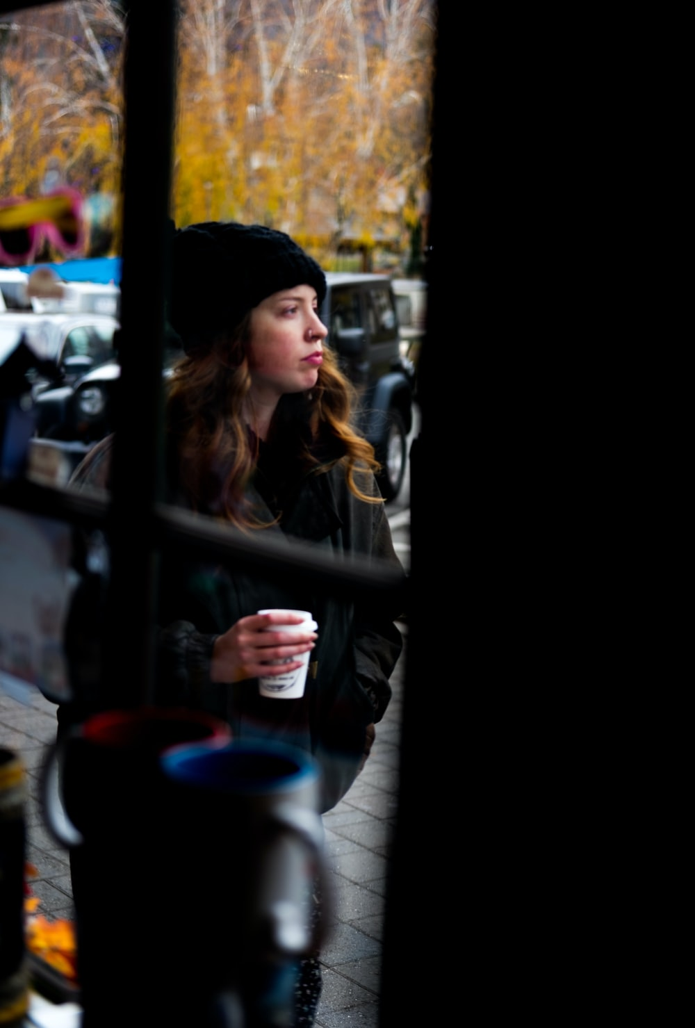 woman in black knit cap holding blue ceramic mug