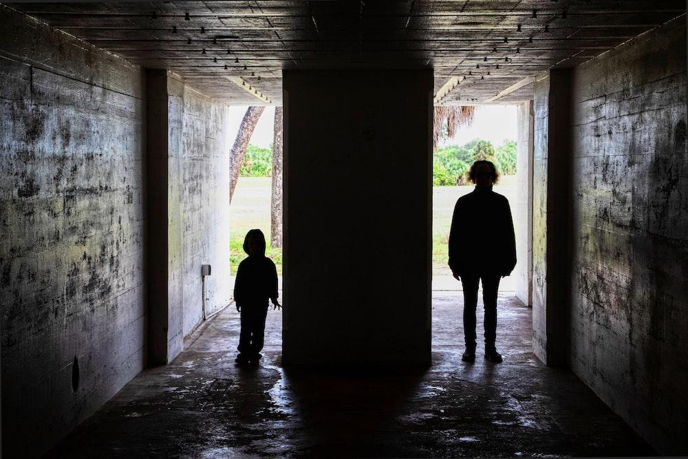 man and woman walking on hallway during daytime