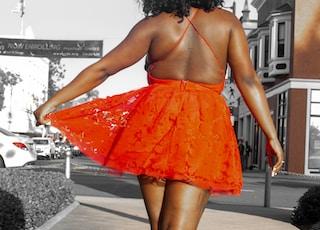 woman in orange skirt standing on gray concrete floor during daytime