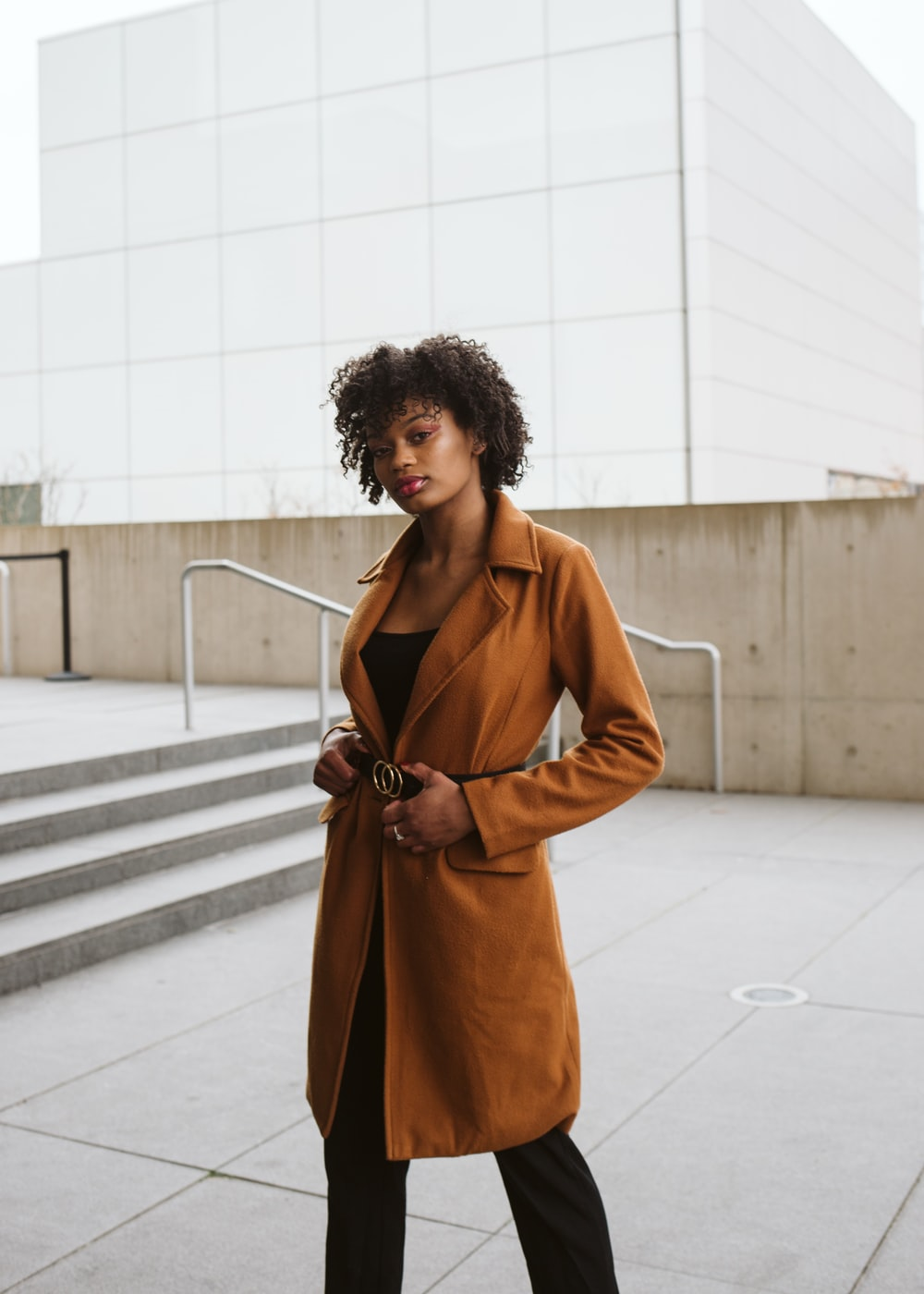 woman in brown coat standing on white floor tiles