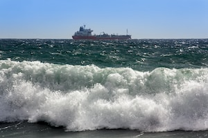red ship on sea waves during daytime