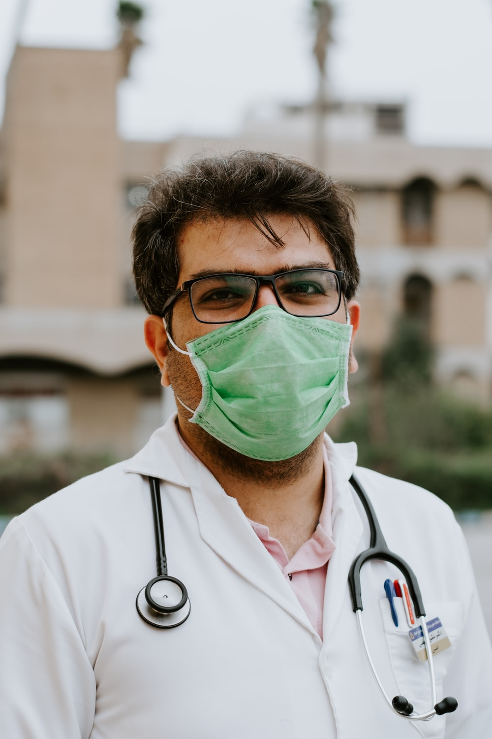 man in white scrub suit wearing green mask