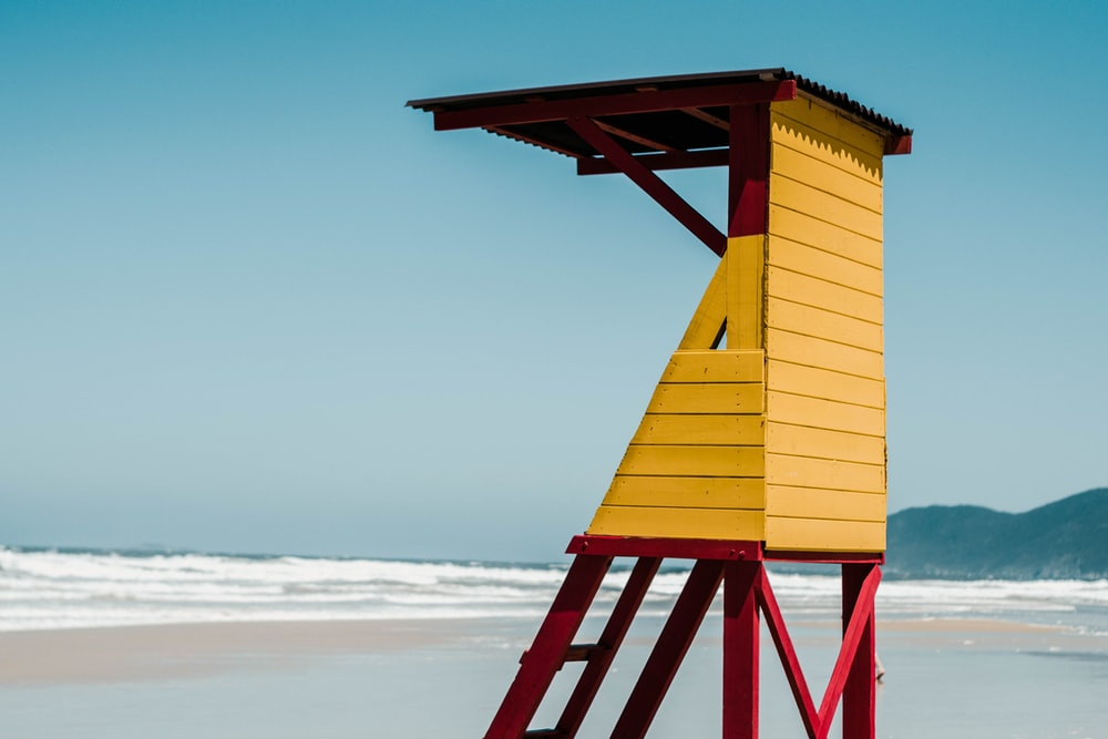 yellow wooden lifeguard tower on beach during daytime