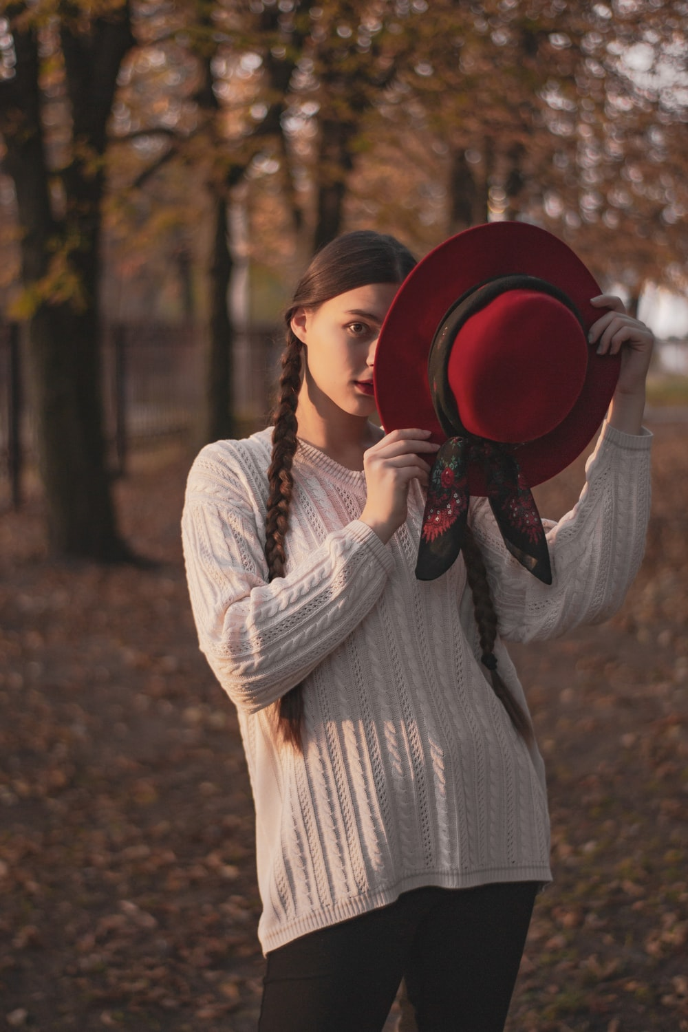 woman in white long sleeve dress holding red hat