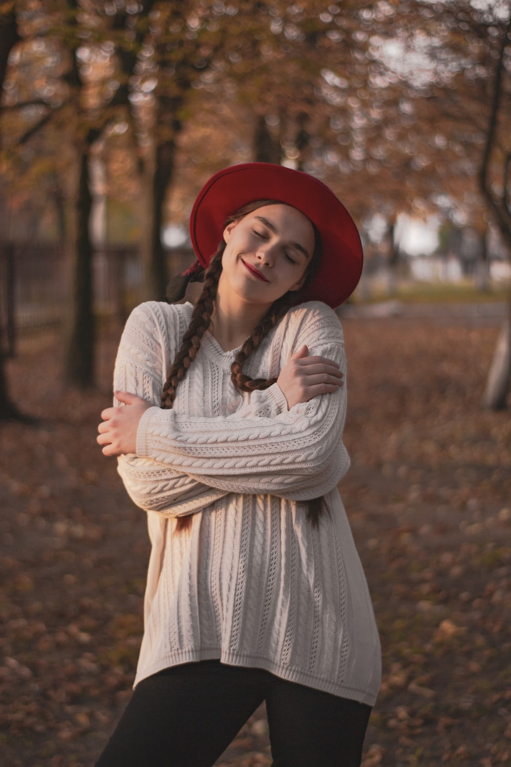woman in red hat and gray long sleeve dress