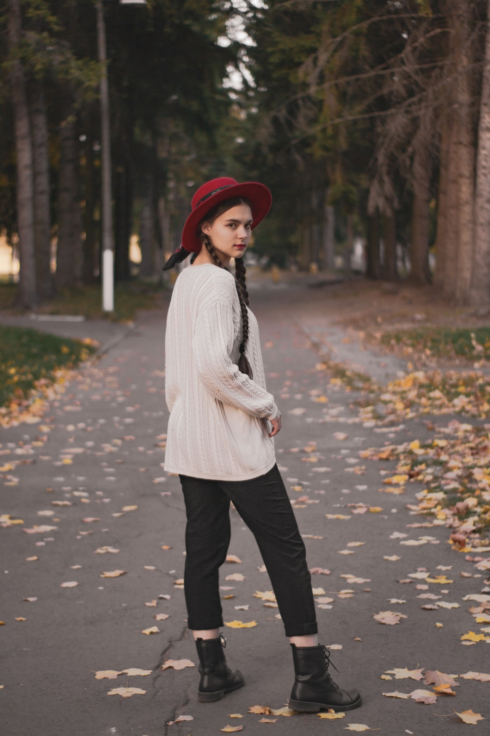 woman in white sweater and black pants standing on road during daytime