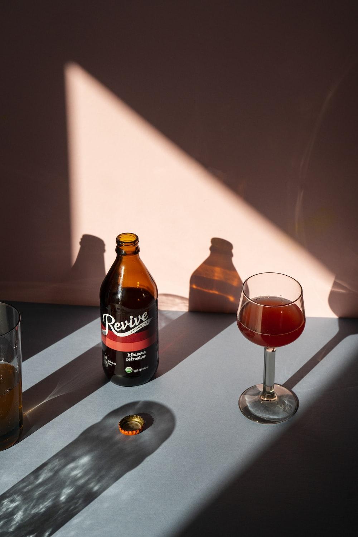 clear wine glass beside black bottle