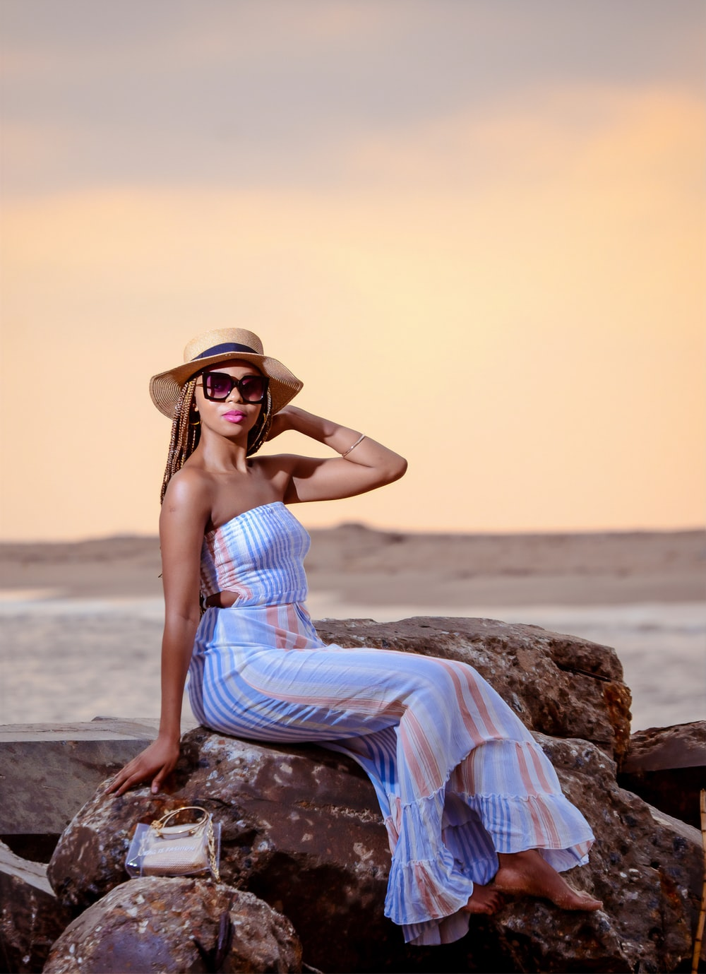woman in blue sleeveless dress sitting on rock near sea during daytime
