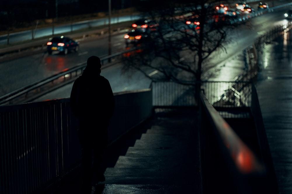 man in black coat standing on sidewalk during night time