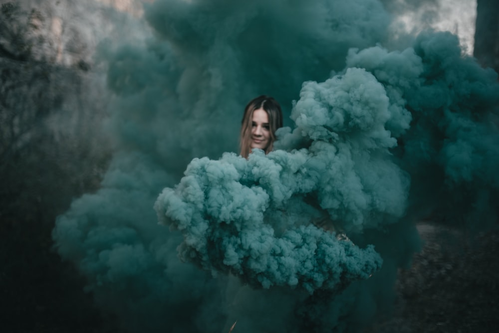 woman in white fur coat standing in front of white smoke