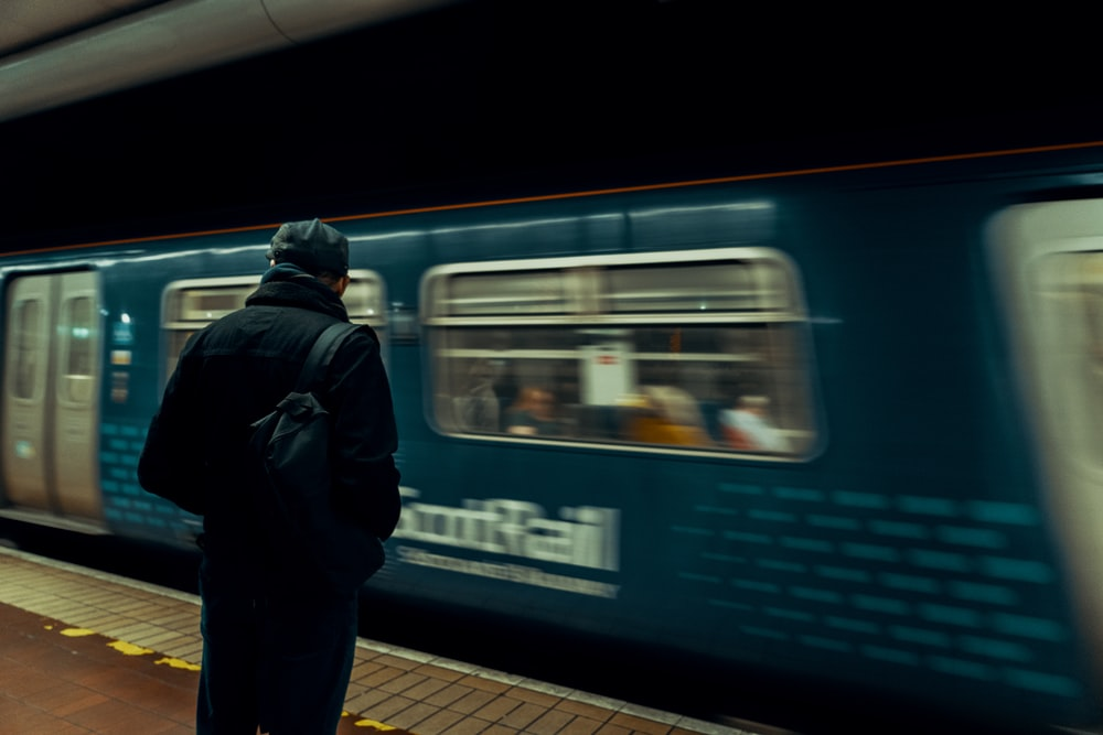 man in black jacket standing beside blue and white train