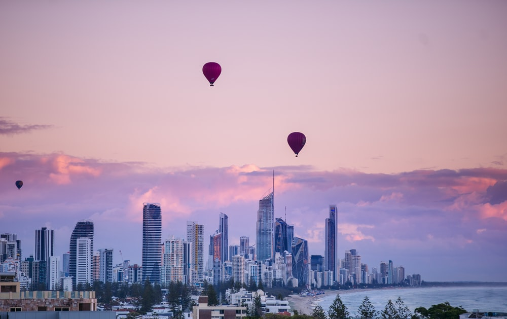 red and blue hot air balloons over city skyline during sunset