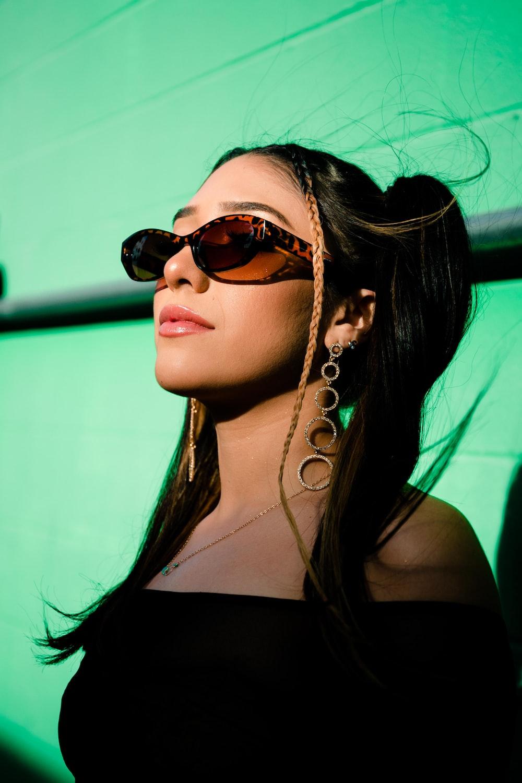 woman in black tank top wearing gold framed aviator sunglasses