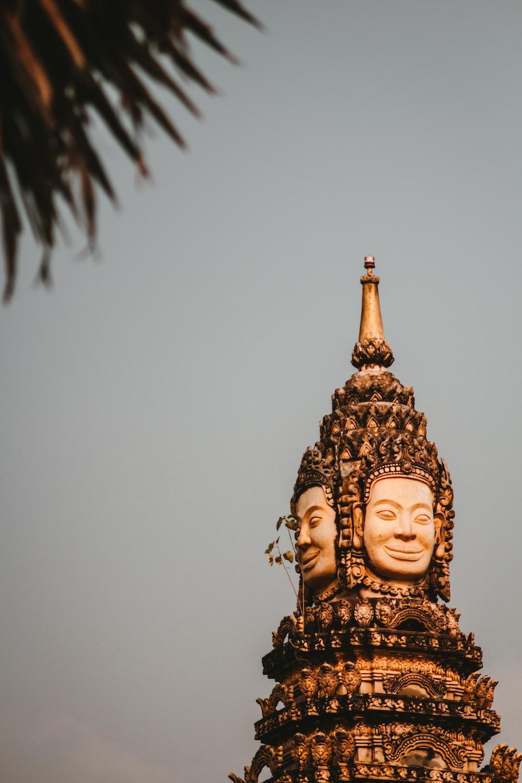 gold buddha statue under gray sky