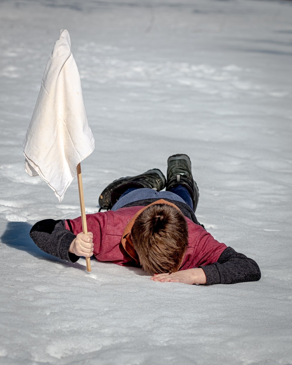 woman in black jacket lying on white snow