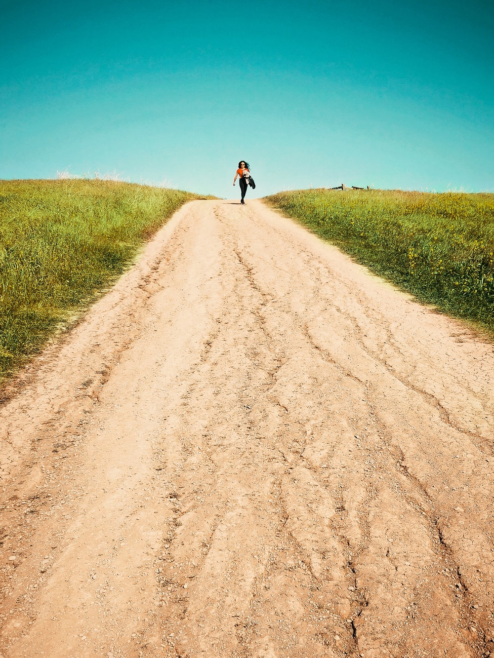 person in black shirt and black pants walking on brown dirt road between green grass field