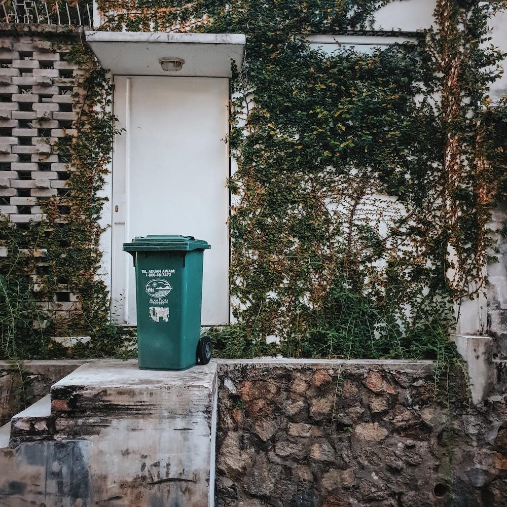 green trash bin beside concrete wall