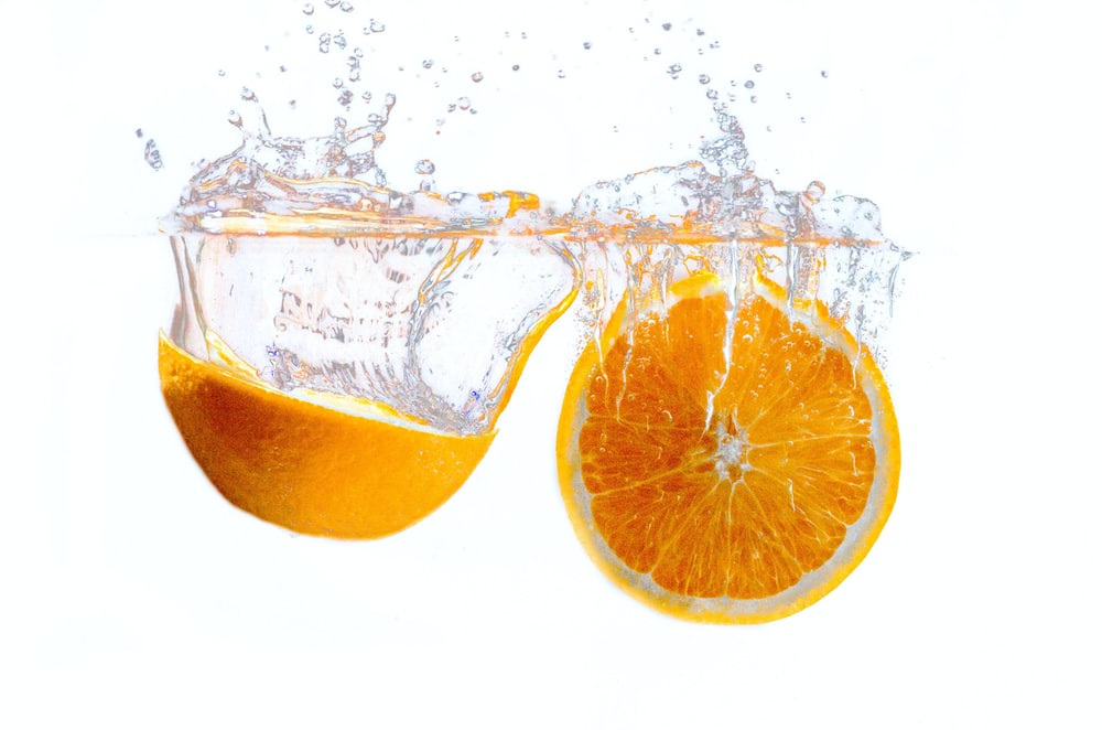 orange fruit in water with white background