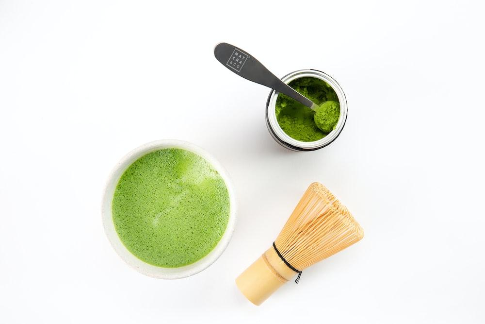 green liquid in white ceramic mug beside brown wooden handled spoon