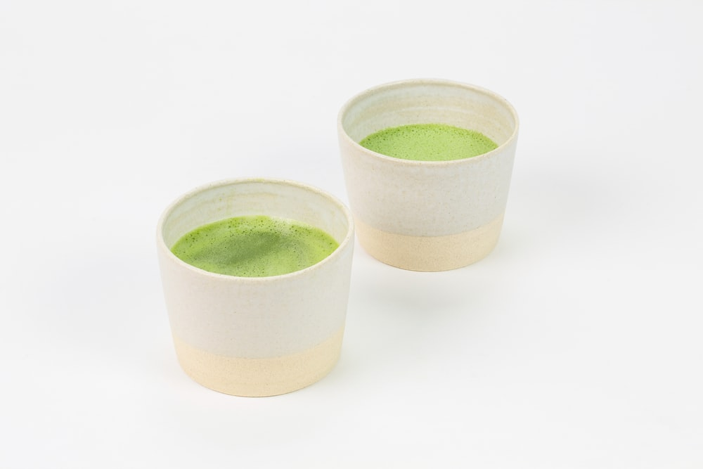 3 green ceramic cups on white surface