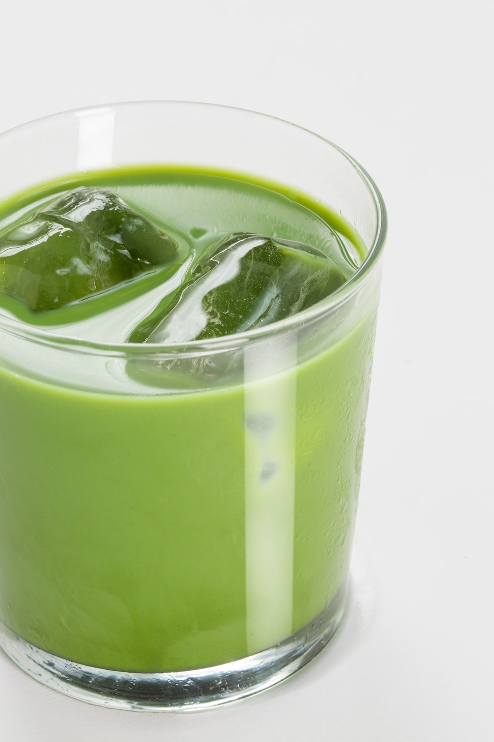 clear drinking glass with green liquid