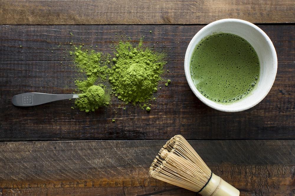 green plant in white ceramic mug beside brown wooden brush