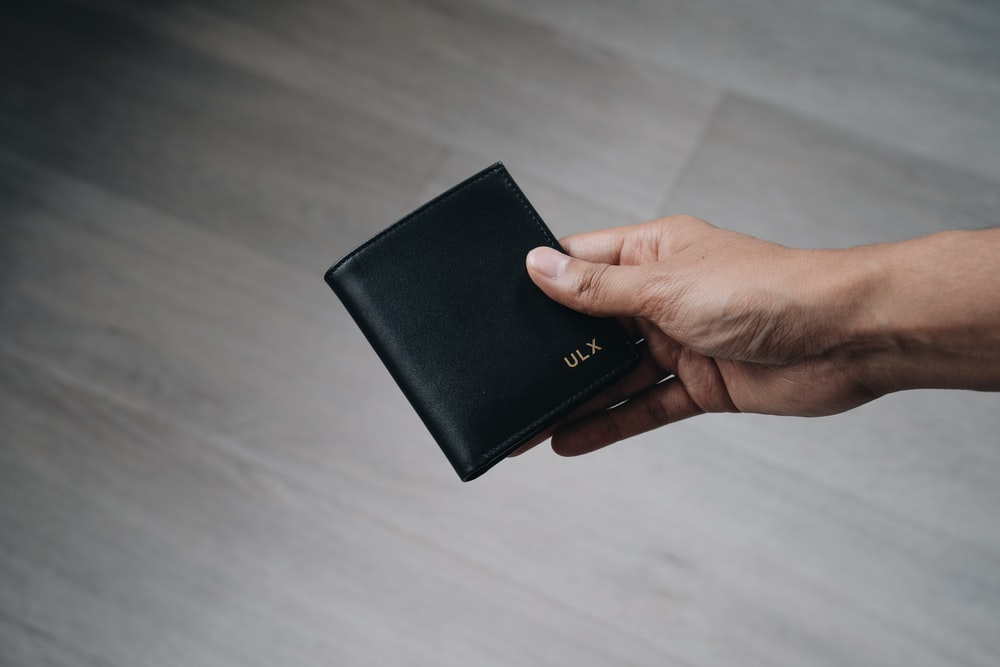 person holding black leather bifold wallet