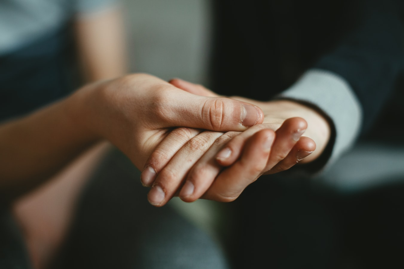 two people holding hands in support and care