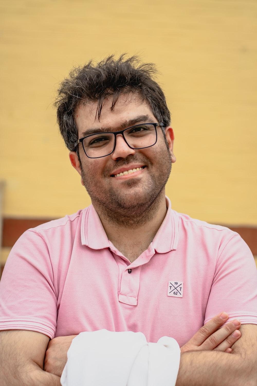 man in pink polo shirt wearing black framed eyeglasses