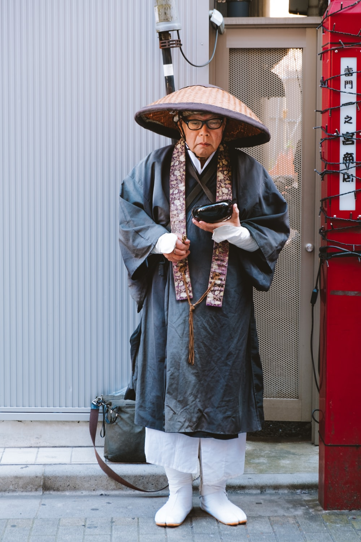 man in blue denim jacket wearing brown hat standing near red door