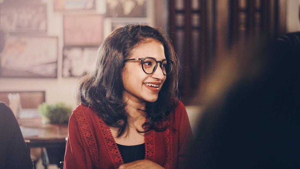 woman in red cardigan wearing black framed eyeglasses