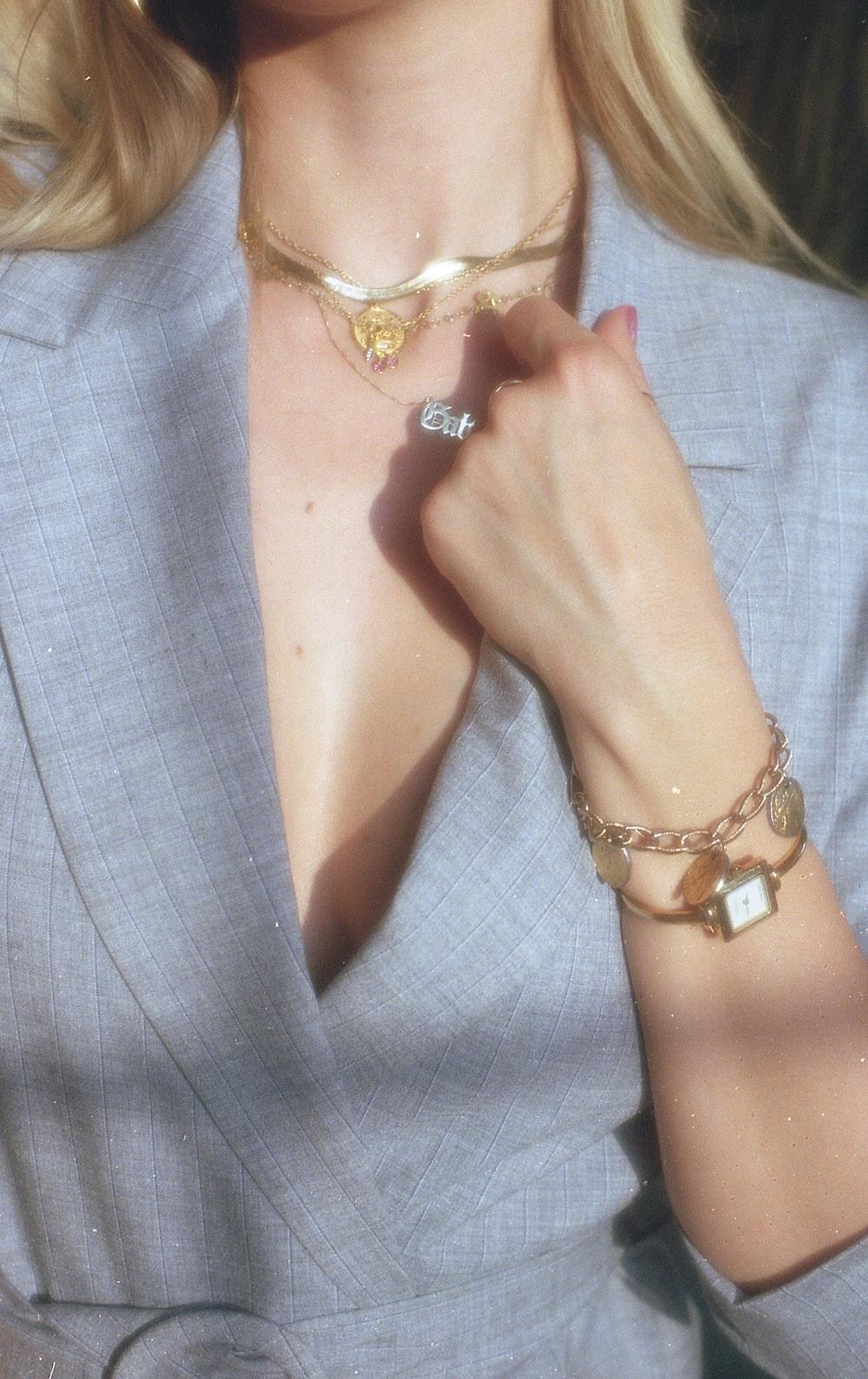 woman in gray blazer wearing gold bracelet and gold bracelet