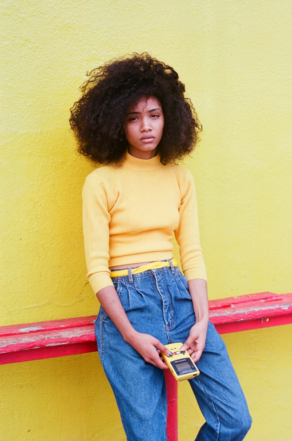woman in yellow turtleneck sweater and blue denim jeans