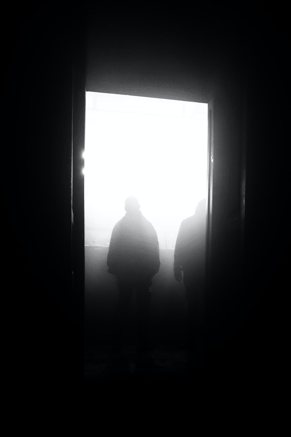 silhouette of man and woman standing in front of window