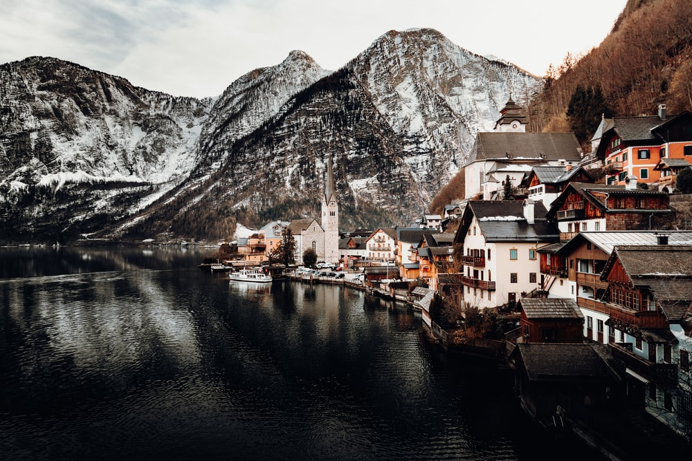 houses near body of water and mountain