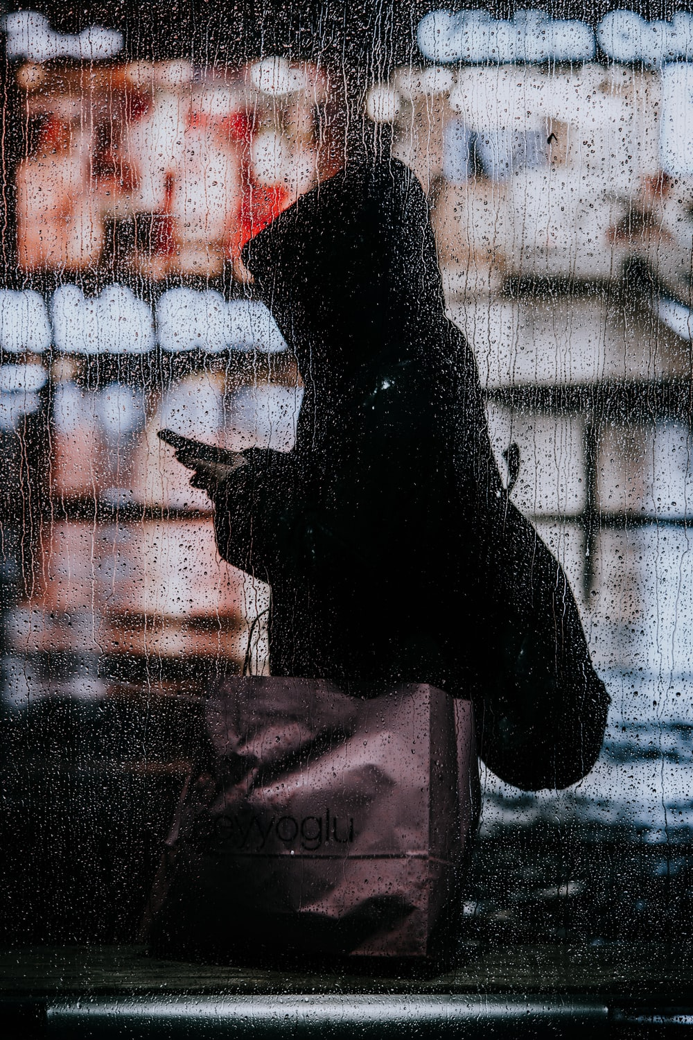silhouette of person in front of glass window