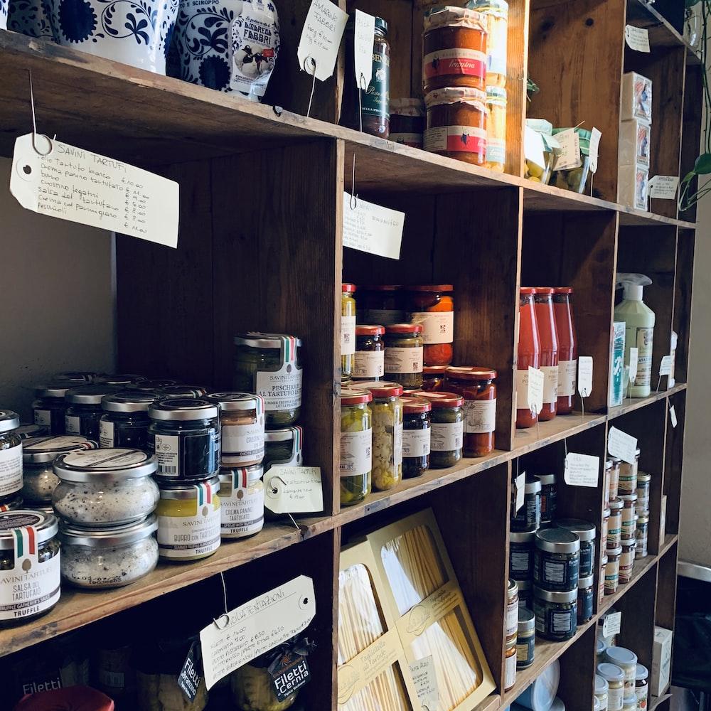 assorted glass jars on brown wooden shelf