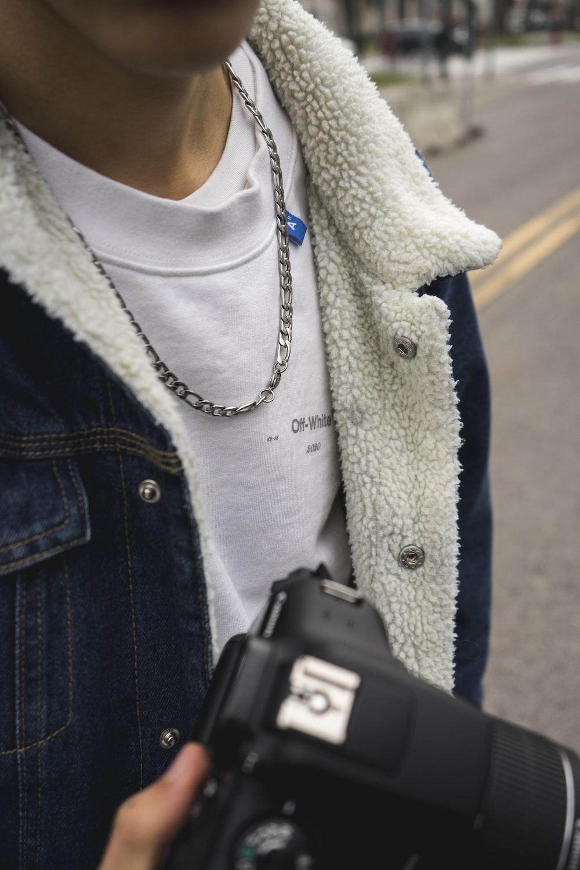 person in blue denim jacket holding black smartphone