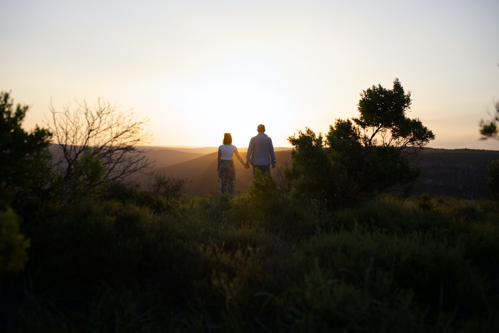 man and woman standing on green grass field during sunset