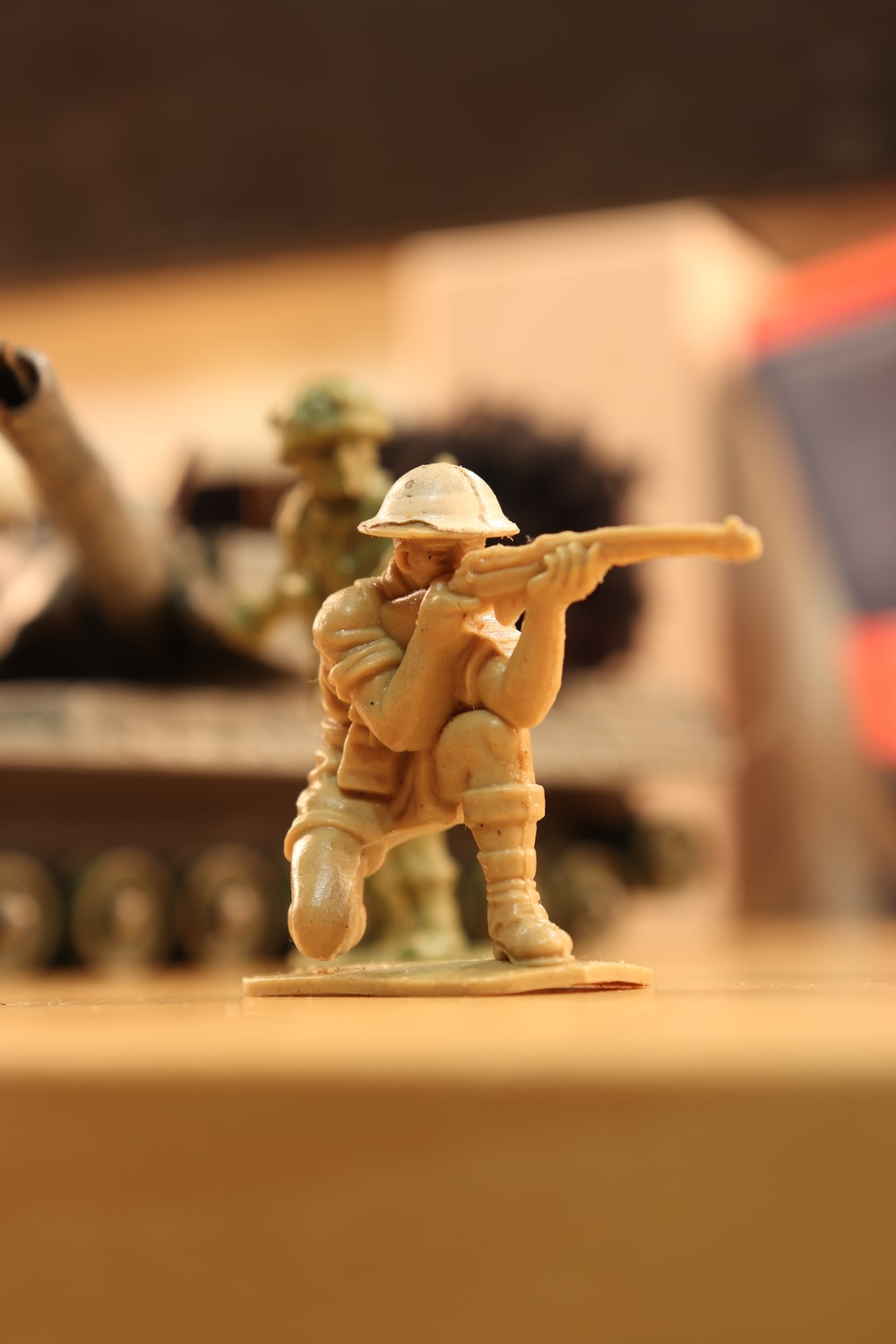 man in brown coat and hat holding rifle figurine