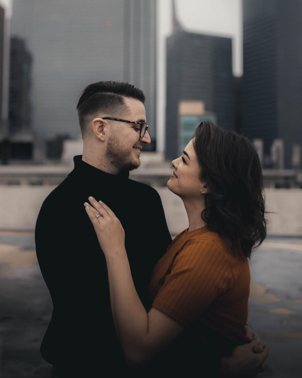 man in black crew neck shirt kissing woman in orange shirt