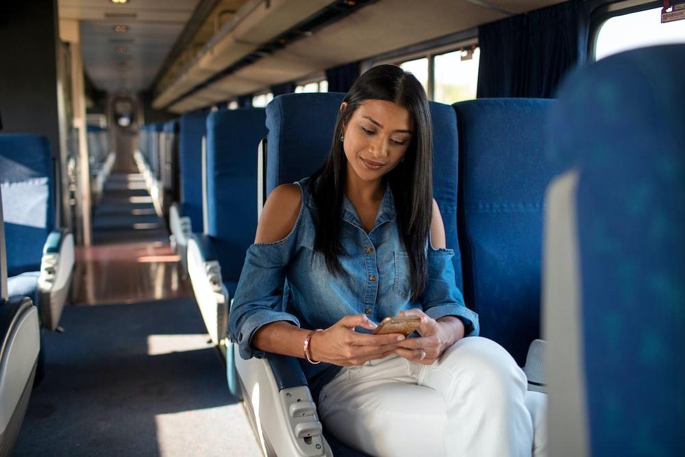 woman in blue denim jacket sitting on blue bus seat