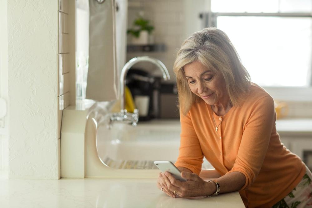 woman in orange long sleeve shirt using white smartphone