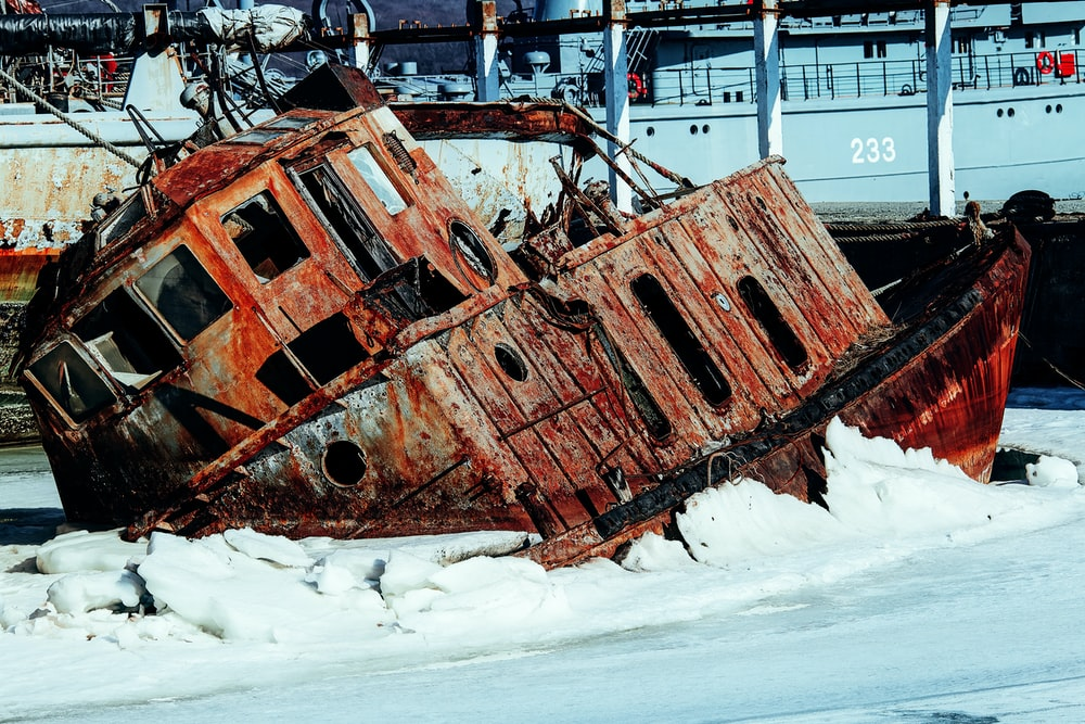 brown and black metal ship on white snow covered ground during daytime