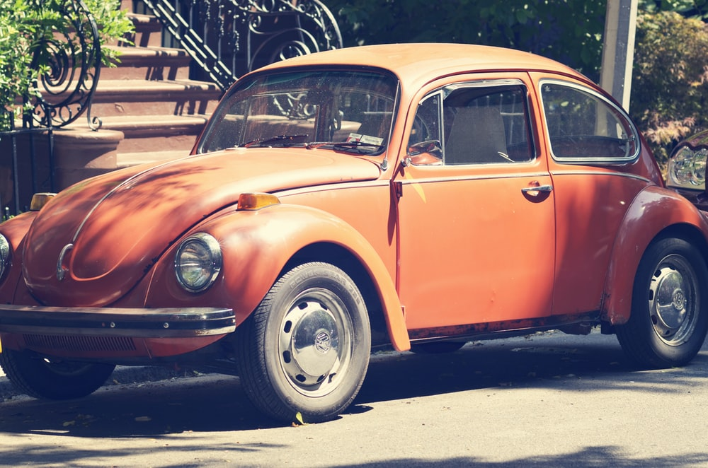 orange volkswagen beetle parked on gray concrete pavement during daytime
