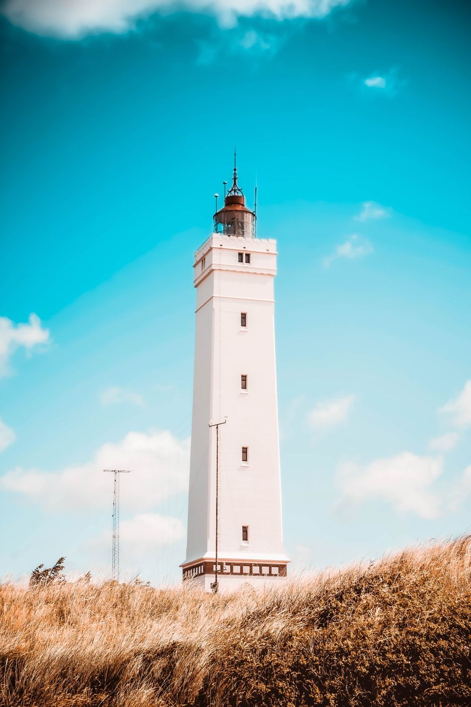 white concrete lighthouse under blue sky during daytime