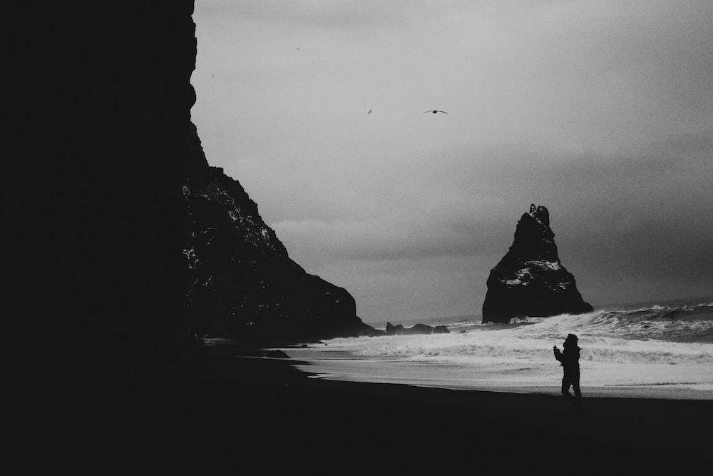 silhouette of 2 people walking on beach shore