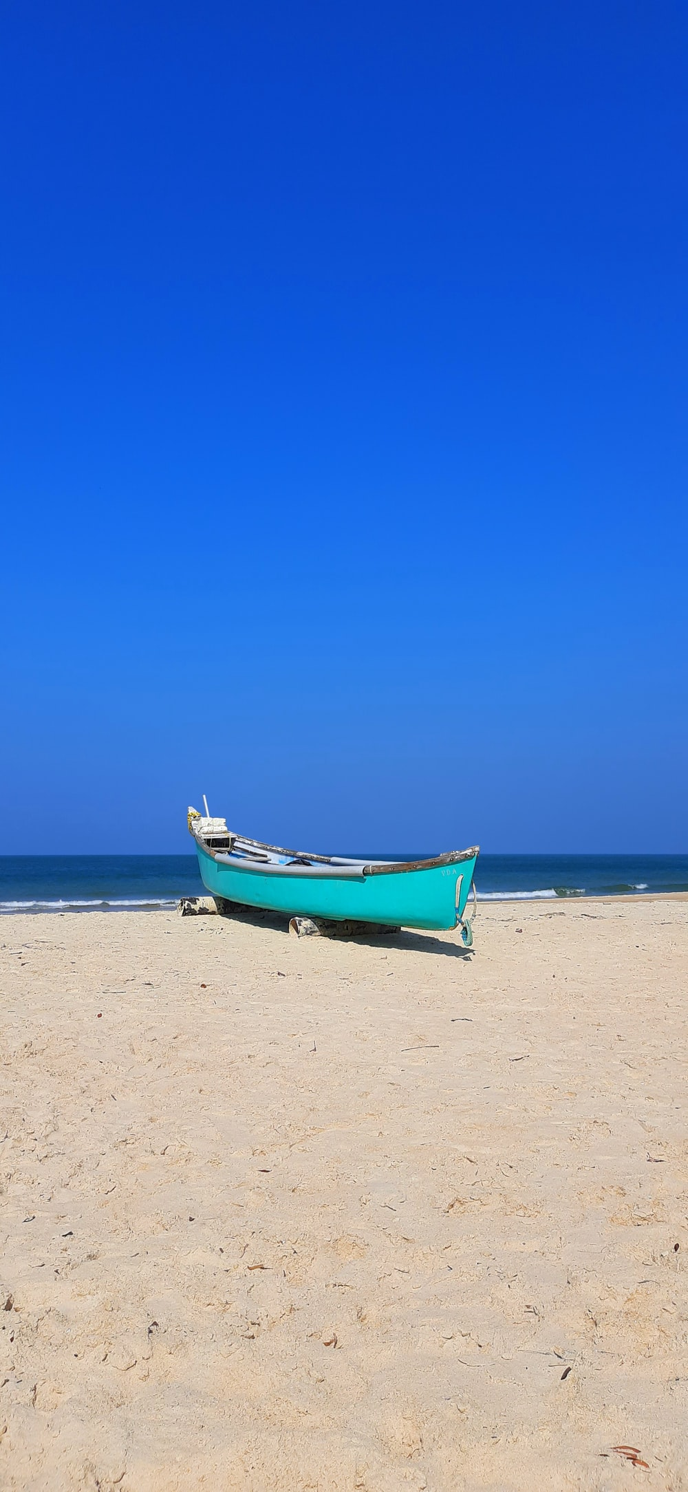 blue and white boat on beach during daytime
