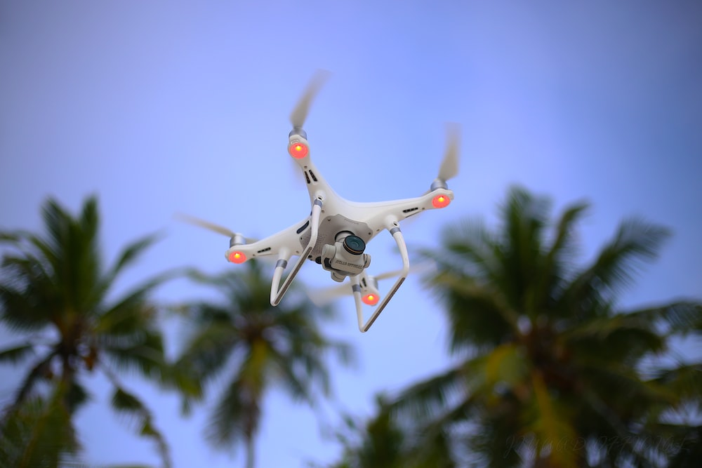 white drone flying in the sky during daytime